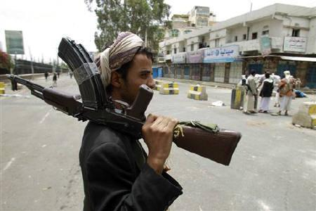 A tribesman loyal to the tribal leader Sadiq al-Ahmar holds his rifle as he secures a street near al-Ahmar's house in Sanaa May 28, 2011. REUTERS/Khaled Abdullah
