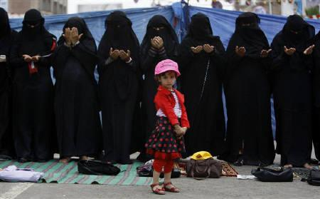 A girl stands in front of praying women during an anti-government rally to demand the ouster of Yemen's President Ali Abdullah Saleh in Sanaa May 28, 2011. REUTERS/Ammar Awad