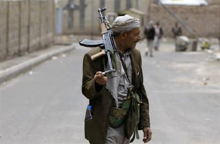 A tribesman loyal to tribal leader Sadeq al-Ahmar hold a rifle as he secures a street near al-Ahmar's house in Sanaa May 28, 2011. REUTERS/Ammar Award