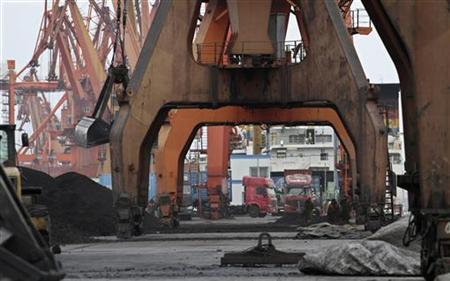 Stevedores walk under giant cranes as they wait to load coal imported from North Korea onto trucks at Dandong port in the Chinese border city of Dandong, Liaoning province December 7, 2010. REUTERS/Stringer