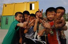 <p>Children of migrant workers pose for a picture outside containers used as classrooms during an after-school program initiated by Compassion for Migrant Children (CMC) in Beijing May 25, 2011. REUTERS/Petar Kujundzic</p>