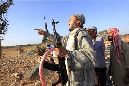 A Libyan rebel fighter shouts ''Allah akbar'' (God is great) as his comrades drive towards the positions of Gaddafi forces at Misrata's western front line, some 25 kilometres from the city centre May 30, 2011. REUTERS/Zohra Bensemra
