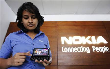 An employee shows a Nokia  E7 model phone to a customer at a Nokia show room in Colombo May 23, 2011. REUTERS/Dinuka Liyanawatte