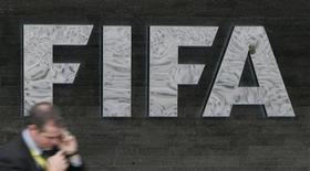 <p>A reporter uses his cell phone as he walks past a FIFA logo in front of FIFA headquarters before a press conference of the FIFA Executive Committee in Zurich October 29, 2007. REUTERS/Michael Buholzer</p>