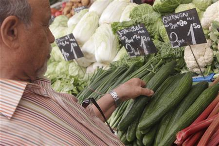 A man selects a cucumber at a vegetable stall at Naschmarkt food market in Vienna May 30, 2011. REUTERS/Herwig Prammer