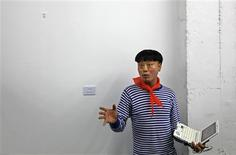 <p>Fei Xiaosheng, an organizer of the Third Incidental Art Festival gestures in front of the wall left blank in support of detained artist-activist Ai Weiwei, during the opening ceremony in Beijing June 1, 2011. Organisers of an art show in the Chinese capital have left an empty space on a gallery wall for detained artist-activist Ai Weiwei in a rare gesture of open defiance over the case. The exhibition comes at an especially sensitive time, as China braces for Saturday's 22nd anniversary of the government's deadly mobilization of the military to clear pro-democracy protests focused on Tiananmen Square in 1989. REUTERS/Petar Kujundzic</p>