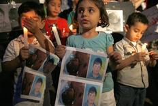 <p>Syrian children carry pictures of 13-year-old Hamza al-Khatib and hold candles during a protest in front of the United Nations building in Beirut June 1, 2011. REUTERS/ Jamal Saidi</p>