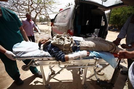 Medics wheel an injured rebel fighter at a field hospital near Misrata's western front line, some 25km from the city center May 31, 2011. REUTERS/Zohra Bensemra
