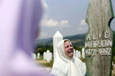 Bosnian Muslim woman Alic Mina (C) cries near the grave of her son Mihrudin before a mass funeral in the village of Memici, about 30 kilometres from Zvornik, June 1, 2011. REUTERS/Dado Ruvic