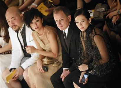 Chinese actress Zhang Ziyi (R) and CEO of Fendi Michael Burke (2nd R) watch models presenting creations during a fashion show of the Italian fashion house, Fendi on the Floating Island on Han River in Seoul June 2, 2011. REUTERS/Lee Jae-Won
