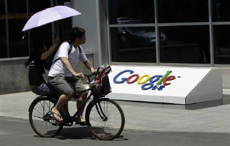 A couple cycle past the logo of Google in front of its former headquarters in Beijing June 2, 2011. REUTERS/Jason Lee