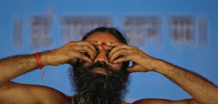 Yoga guru Swami Ramdev performs yoga at the Ramlila grounds on the first day of his fast in New Delhi June 4, 2011. REUTERS/Adnan Abidi