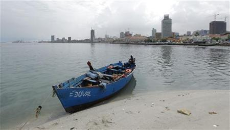 An Angolan fisherman sits by his boat against the backdrop of the capital Luanda January 20, 2010. REUTERS/Mike Hutchings