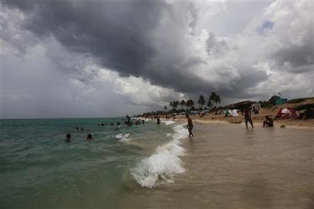 People swim in the sea as a tropical shower forms in the sky on the outskirts of Havana July 15, 2010. REUTERS/Desmond Boylan