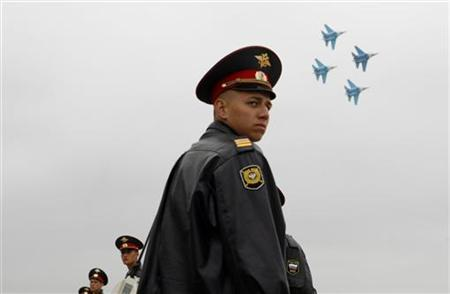 Policemen stand guard as a Russian Air Force aerobatic team performs at the Moscow International Air Show in Zhukovsky, August 23, 2009. REUTERS/Denis Sinyakov