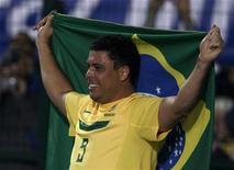 O jogador Ronaldo segura uma bandeira do Brasil jogada pela torcida no intervalo de sua última partida pela seleção brasileira, contra a Romênia, no estádio do Pacaembu, em São Paulo. 07/06/2011 REUTERS/Paulo Whitaker