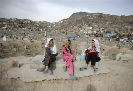 Girls, who sell water, sit on a grave at a cemetery in Kabul June 5, 2011. REUTERS/Mohammad Ismail