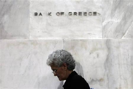 A woman walks in front of the Bank of Greece in Athens, June 3, 2011. REUTERS/John Kolesidis/Files