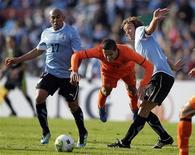 Ibrahim Afellay (centro), da Holanda, Egido Rios (esquerda) e Diego Lugano (direita), do Uruguai, em amistoso em Montevidéu, Uruguai. 08/06/2011  REUTERS/Andres Stapff