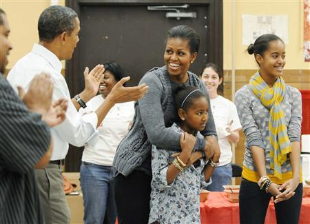 First Lady Michelle Obama (C), holding her daughter Sasha, arrives with her husband President Barack Obama (L) and daughter Malia (R) to volunteer in honor of Martin Luther King Jr Day at Stuart-Hobson Middle School on Capitol Hill in Washington in this January 17, 2011 file photo. REUTERS/Jonathan Ernst/Files