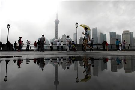 People walk at the Bund along the Huangpu River after two days of heavy rain in Shanghai June 7, 2011. REUTERS/Carlos Barria