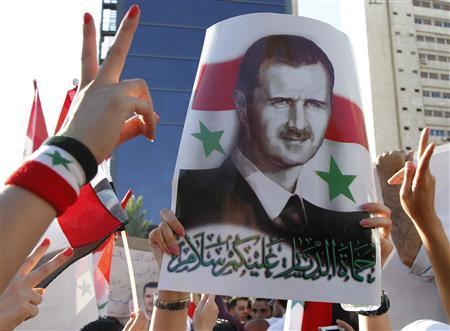 A pro-Syrian President Bashar al-Assad supporter, who rallied to a Facebook call to sit-in to support the army at Arnous square, carries his picture in Damascus June 7, 2011 ,after the Syrian troops with tanks moved on Tuesday towards Jisr al-Shughour town, where the government has vowed to quell a revolt after accusing gunmen of killing scores of security men. REUTERS/Khaled al-Hariri