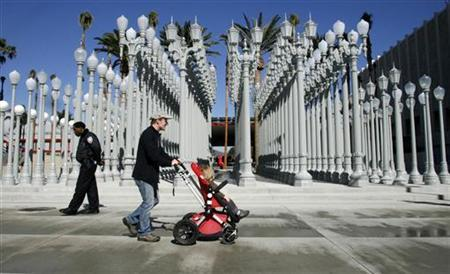 A man pushes a stroller as a security guard walks past the ''Urban Light'' installation by artist Chris Burden at the Broad Contemporary Art Museum in the Los Angeles County Museum of Art campus February 7, 2008. REUTERS/Fred Prouser