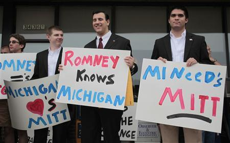 Dillon Breen (2nd R) and John Dalton (R) hold signs of support while they wait for Republican presidential candidate Mitt Romney to arrive at a Coney Island Restaurant in Livonia, Michigan June 9, 2011. REUTERS/Rebecca Cook