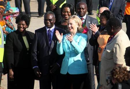 US Secretary of State Hillary Clinton claps as she is greeted by dancers on arrival in the Zambian capital Lusaka June 10, 2011. REUTERS/Mackson Wasamunu
