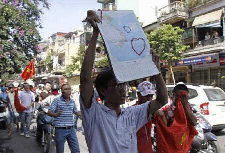 An anti-China protester holds a map of Vietnam with the islands of Paracel and Spratly marked out during a protest march on a street in Hanoi June 5, 2011. REUTERS/Kham