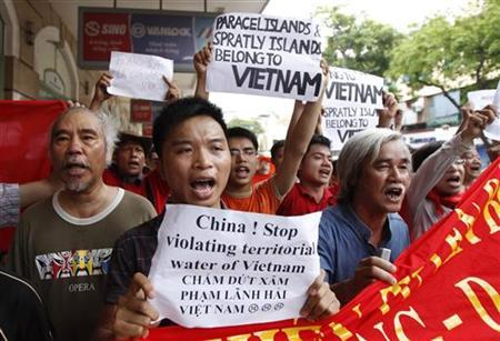 Art director Do Minh Tuan (L), writer Pham Xuan Nguyen (2nd R) march with anti-China protesters during a demonstration in Hanoi June 12, 2011. REUTERS/Kham
