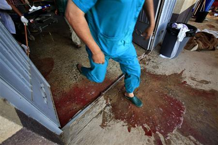 A Libyan medic walks while volunteers remove blood at a field hospital near Misrata's western frontline, June 12, 2011. REUTERS/Zohra Bensemra