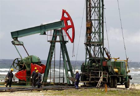 Men work at an oil pump near the coast on the outskirts of Havana June 10, 2011. REUTERS/Enrique De La Osa