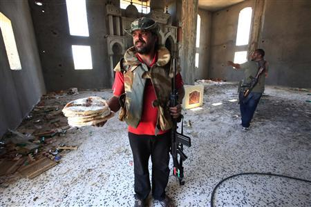 A Libyan rebel fighter distributes pizzas to his comrades inside a mosque taken from forces loyal to Muammar Gaddafi, after rebels pushed several kilometres in the direction of Zlitan, west of the rebel-held port city of Misrata, June 13, 2011. REUTERS/Zohra Bensemra