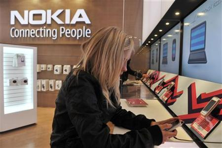 A girl tests out the new Nokia N8 mobile phone at the Nokia Flagship store in Helsinki September 10, 2010. REUTERS/Markku Ulander/Lehtikuva