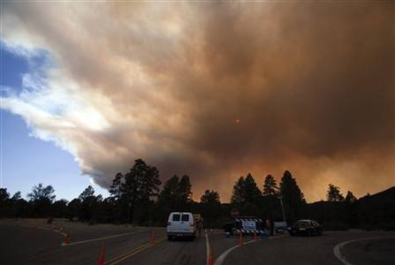 Smoke from the Wallow Wildfire obscures the sun at a road check point west of the Reserve, New Mexico June 13, 2011. REUTERS/Jim Urquhart