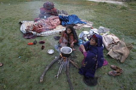A migrant woman and her daughter make breakfast in a park during the early hours in Srinagar June 13, 2011. India is ranked fourth in the world's most dangerous countries for women due to a barrage of threats ranging from violence and rape to dismal healthcare and ''honour killngs'', a Thomson Reuters Foundation poll shows.  REUTERS/Fayaz Kabli
