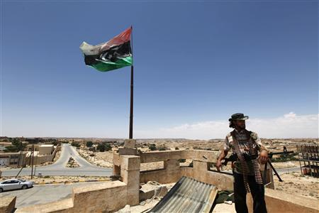 A rebel fighter looks out from the roof of a house, that previously had been used as an observation post for forces loyal to Libya's leader Muammar Gaddafi, in the city of Kikla, about 150 km (90 miles) southwest of Tripoli, June 14, 2011. REUTERS/Anis Mili