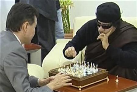 A frame from footage provided by the FIDE Press service shows Libyan leader Muammar Gaddafi (R) playing chess with visiting president of the World Chess Federation Kirsan Ilyumzhinov before a game of chess in Tripoli, June 12, 2011. REUTERS/FIDE Press service/Handout