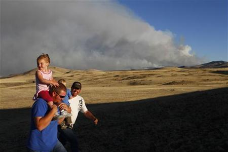 Colt Groff, carrying his daughter Peyton Groff (L), and Jason Hill, carrying Trayson Groff, look at the smoke from the Wallow wildfire in Apache County, Arizona June 9, 2011. REUTERS/Joshua Lott