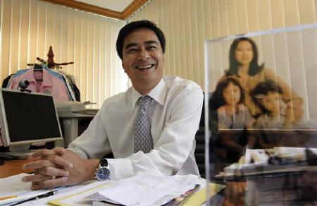 Thailand's Prime Minister Abhisit Vejjajiva smiles behind a photo of his family as he talks to reporters in his office in Bangkok June 14, 2011. REUTERS/Sukree Sukplang