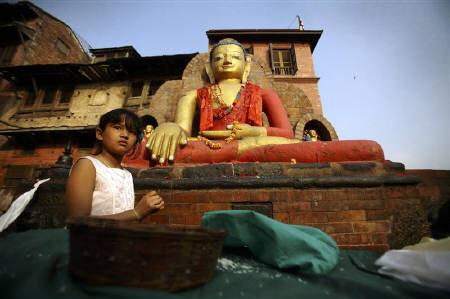 A girl sells lamps filled with clarified butter or ghee in front of a statue of Buddha at Swyambhu during celebrations of the birth anniversary of Buddha in Kathmandu May 17, 2011. REUTERS/Navesh Chitrakar/Files