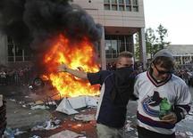 Torcedores do Vancouver Canucks passam em frente a uma caminhoete incendiada no centro de Vancouver, no Canadá, após cenas de violência que seguiram a derrota dos Canucks contra os Boston Bruins. 16/06/2011 REUTERS/Anthony Bolante