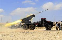 """Повстанцы стоят рядом с ракетной установкой """"Град"""" на линии фронта к западу от города Мисурата 17 июня 2011 года. Самолеты НАТО в пятницу продолжили бомбежки Триполи, после того как сын Муаммара Каддафи сообщил о готовности ливийского лидера решить спор на выборах. Это предложение не устроило и США.  REUTERS/Zohra Bensemra"""