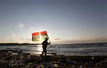 A Libyan man walks with a Kingdom of Libya flag near the Sea of Benghazi June 16, 2011. REUTERS/Mohamed Abd El-Ghany