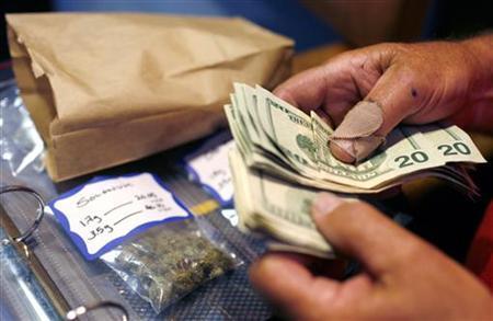 A customer makes a medical marijuana purchase at the Coffeeshop Blue Sky dispensary in Oakland, California June 30, 2010. REUTERS/Robert Galbraith