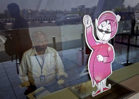 An Air India ticketing staff member sits at a closed counter in front of the Air India mascot at their ticket office at the domestic airport in Mumbai April 27, 2011.  REUTERS/Vivek Prakash/Files