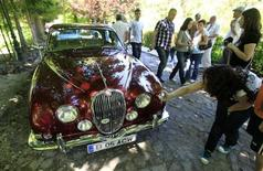 "<p>A visitor takes pictures of a Jaguar XK150 during Romania's first ""Vintage Cars Elegance Contest"" organised in Sinaia mountain resort in front of Peles royal castle, 140 km north of Bucharest May 28, 2011. REUTERS/Bogdan Cristel</p>"