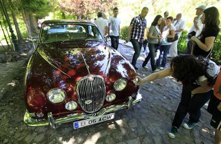 A visitor takes pictures of a Jaguar XK150 during Romania's first ''Vintage Cars Elegance Contest'' organised in Sinaia mountain resort in front of Peles royal castle, 140 km north of Bucharest May 28, 2011. REUTERS/Bogdan Cristel
