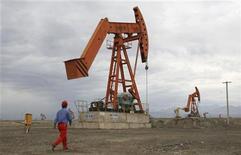 <p>An employee walks towards a pump jack at a PetroChina plant in Shanshan county of Hami, Xinjiang Uigur Autonomous Region July 24, 2008. REUTERS/Stringer</p>